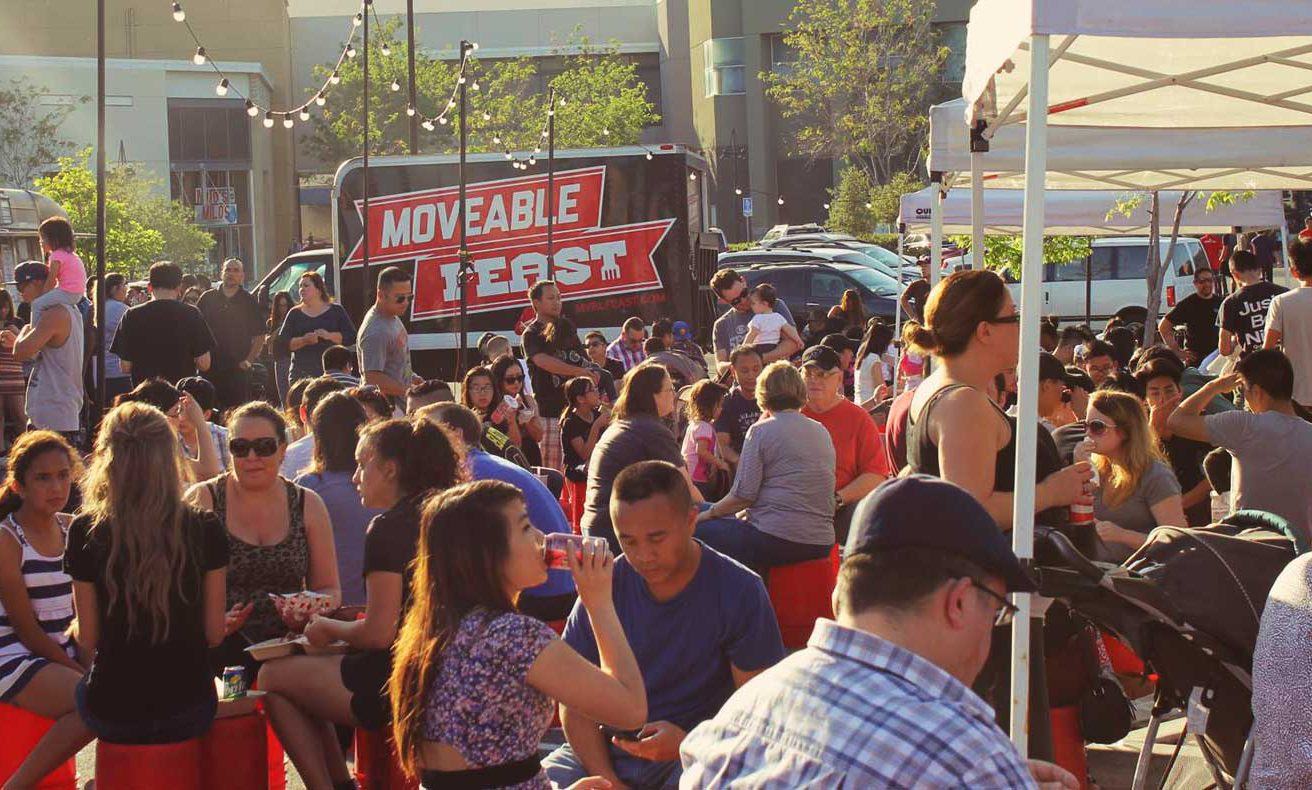 A crowd of folks nosh on food from food trucks
